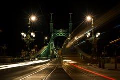 过自由桥梁的电车和汽车夜视图在布达佩斯,匈牙利 免版税图库摄影