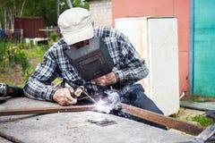年迈的人焊接金属建筑 免版税库存图片