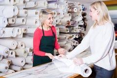 年迈的卖主显示织品给年轻买家 图库摄影