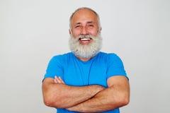 年迈的有胡子的适合人用横渡的手和开朗的笑反对 免版税图库摄影