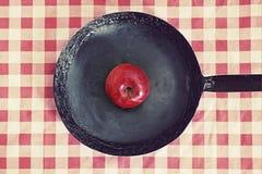 年迈的煎锅用红色苹果 免版税图库摄影