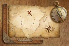 年迈的珍宝地图、统治者和古金色指南针在木桌上 库存照片