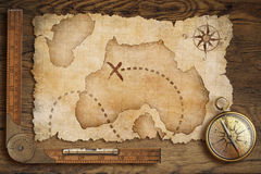 年迈的珍宝地图、统治者和老古铜色指南针在桌上 图库摄影