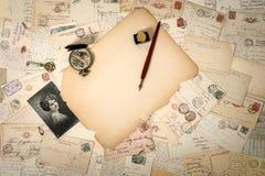 年迈的纸、古色古香的辅助部件和老明信片 葡萄酒后面 免版税库存图片