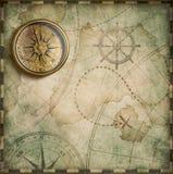 年迈的黄铜古色古香的船舶指南针和老珍宝地图 免版税库存照片