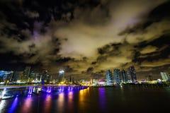 迈阿密市黄昏的地平线全景与都市摩天大楼和桥梁在海有反射的 库存图片