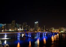 迈阿密市黄昏的地平线全景与都市摩天大楼和桥梁在海有反射的 图库摄影