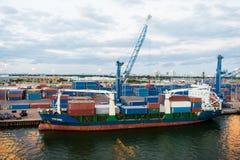 迈阿密,美国- 2016年3月01日:在海容器口岸的货船与容器和起重机 口岸或终端多云天空的 Fre 库存图片
