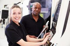 运作与CNC机器的工程师的学徒画象 免版税库存图片