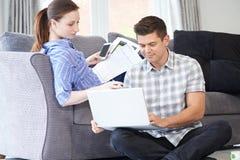 运作从家的自由职业者的夫妇一起看膝上型计算机 免版税库存图片
