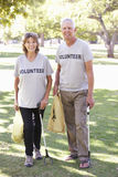 运作作为志愿小组清洁废弃物一部分的资深夫妇在公园 库存照片