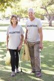 运作作为志愿小组清洁废弃物一部分的资深夫妇在公园 免版税库存图片