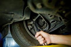 运作在一辆被举的汽车下的汽车机械师的元素 图库摄影