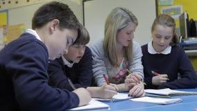 运作在与帮助他们的老师的表上的学生 影视素材