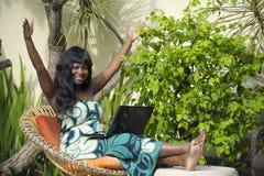 运作在与愉快的膝上型计算机的豪华大阳台别墅的庄重装束的愉快的黑人美国黑人的妇女激动和 免版税库存照片