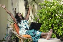 运作在与愉快的膝上型计算机的豪华大阳台别墅的庄重装束的愉快的黑人美国黑人的妇女激动和 库存图片
