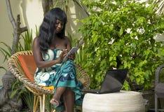 运作在与膝上型计算机和手机的豪华大阳台别墅的庄重装束的愉快的黑人美国黑人的妇女 免版税库存照片