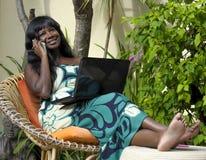 运作在与膝上型计算机的豪华大阳台别墅的庄重装束的愉快的黑人美国黑人的妇女谈话在手机 免版税库存图片
