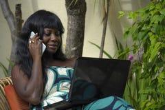 运作在与膝上型计算机的豪华大阳台别墅的庄重装束的愉快的黑人美国黑人的妇女谈话在手机 免版税库存照片