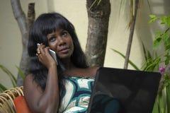 运作在与膝上型计算机的豪华大阳台别墅的庄重装束的愉快的黑人美国黑人的妇女谈话在手机 图库摄影