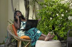 运作在与膝上型计算机的豪华大阳台别墅的庄重装束的愉快的黑人美国黑人的妇女谈话在手机 免版税图库摄影