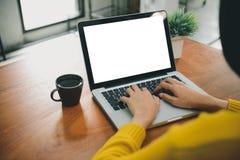 运作在办公室外的数字式生活方式 妇女递有黑屏的键入的便携式计算机在咖啡店的桌上 免版税图库摄影