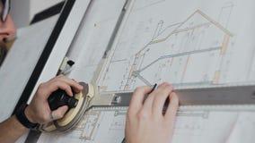 运作在办公室居民住房的图纸的男性建筑师特写镜头 股票录像