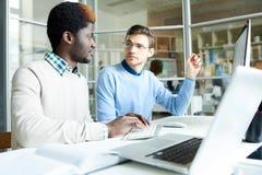 运作在办公室的两位IT程序员 免版税库存照片
