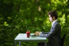 运作在办公桌上的膝上型计算机的商人旁边画象在绿色公园 到达天空的企业概念金黄回归键所有权 免版税图库摄影