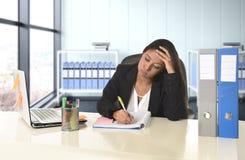运作在办公计算机书桌的年轻绝望女商人痛苦重音 图库摄影