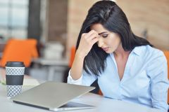 运作在办公计算机的年轻繁忙的美好的拉丁女商人痛苦重音 免版税库存图片