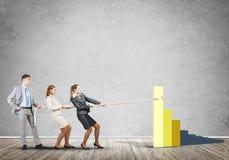 运作在合作的Businessteam拉扯与绳索的图表作为力量和控制的标志 免版税库存照片