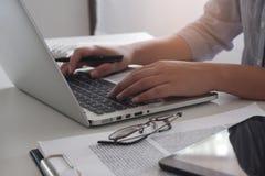 运作在她的办公室的专业女实业家的播种的图象通过使用笔记本电脑设备的膝上型计算机年轻女性经理 免版税图库摄影