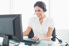 运作在她的在电话的书桌的快乐的电话中心代理 库存图片