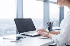 运作在家庭办公室的妇女侧视图画象当远程工作人员,键入的和冲浪的互联网,有工作天 免版税图库摄影