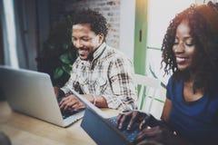 运作在家的非洲夫妇:使用触板和笑的黑人女孩,看通过旅行照片与一起 免版税库存照片