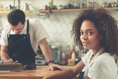 运作在宽敞的咖啡馆的发款员和waitperson 免版税库存图片
