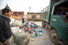 从运作在排序的更加恶劣的区域的人们在转储的塑料,在加德满都,尼泊尔 免版税库存图片