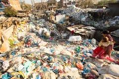 从运作在排序的更加恶劣的区域的未认出的人在转储的塑料, 2013年12月22日在加德满都,尼泊尔 库存照片