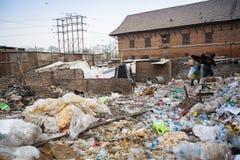 从运作在排序的更加恶劣的区域的未认出的人在转储的塑料, 2013年12月19日在加德满都 免版税库存图片