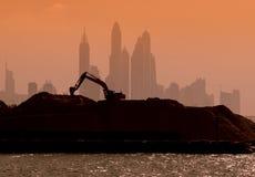 运作在摩天大楼背景的挖掘机剪影  免版税库存图片