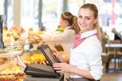 运作在收款机的面包店的店主 免版税图库摄影