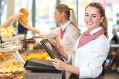 运作在收款机的面包店的店主 免版税库存照片