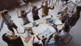 运作在时髦顶楼办公室的企业队顶视图 年轻混合的族种人在中心上一起把棕榈放 免版税库存图片