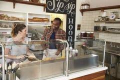 运作在柜台后的混合的族种夫妇在三明治酒吧 库存照片