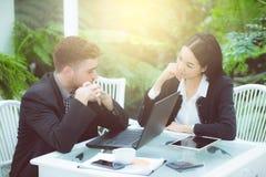 运作在现代办公室的年轻事务夫妇,谈论两个的工友乐趣射出在膝上型计算机 免版税库存图片