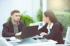 运作在现代办公室的年轻事务夫妇,谈论两个的工友乐趣射出在膝上型计算机 免版税库存照片