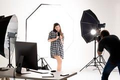 运作在现代照明设备演播室的摄影师和俏丽的模型 图库摄影