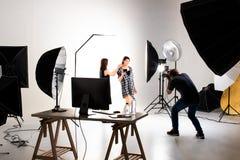 运作在现代照明设备演播室的摄影师和俏丽的模型 免版税库存图片