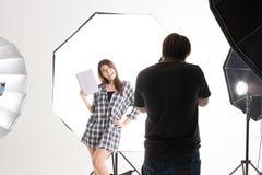 运作在现代照明设备演播室的摄影师和俏丽的模型 库存图片